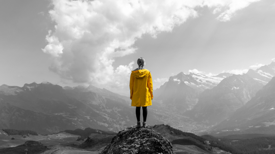 Woman in a rain coat standing on a mountain top   SV Partners